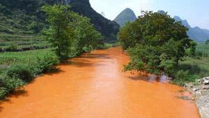 Ảnh 2: Tác động ô nhiễm môi trường nơi khai thác bauxite tại Tịnh Tây, Quảng Tây 10 - 8-2008 Suối Tịnh Tây trong xanh trở thành suối máu (Ảnh do Dương Danh Dy sưu tầm).